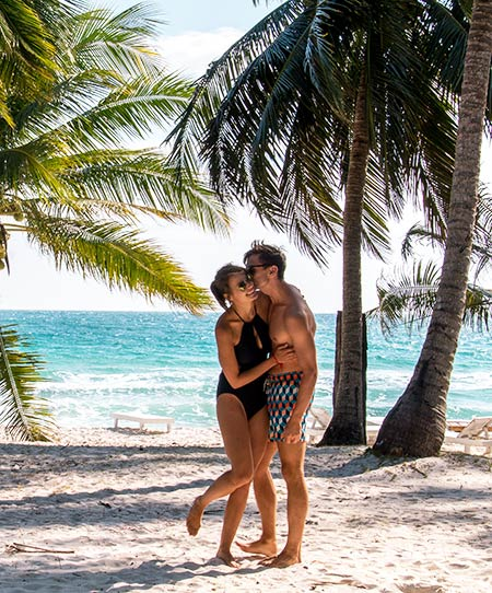 two people kissing on white sand beach with coconut trees and blue ocean on Koh Rong in Cambodia