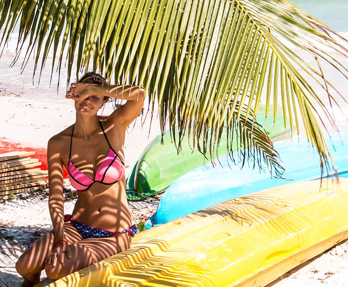 woman in pink swimwear sitting on yellow kayak with blue and green kayak in back-round on Koh Rong in Cambodia