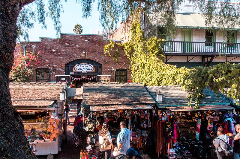 souvenir stalls and people buying things at El Pueblo, green tree and red brick building