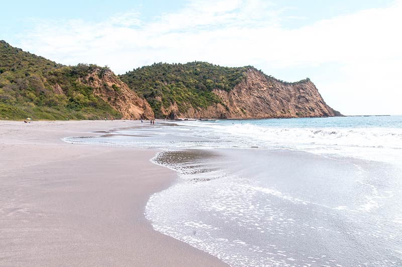 white sand, brown rocks and blue water on Los Frailes in Ecuador
