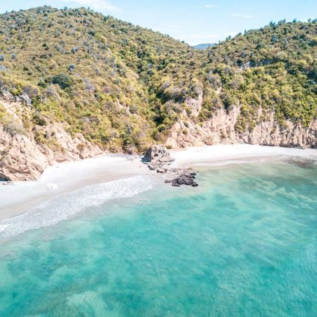 white cliff, green hills and blue emerald waters on Los Frailes in Ecuador