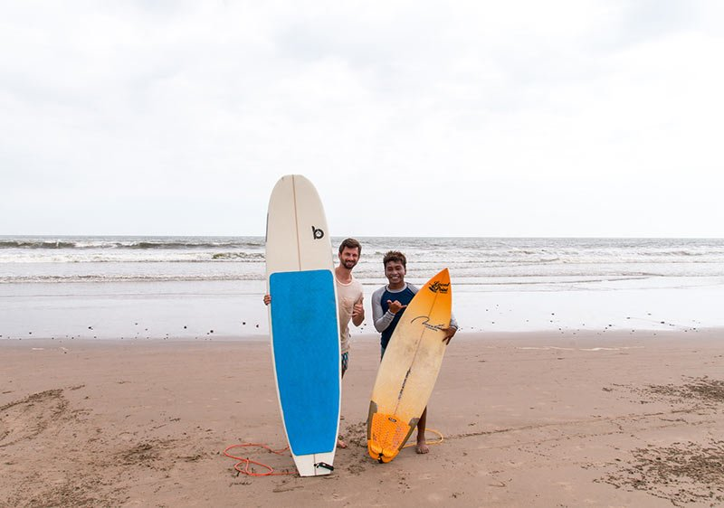 two people holding yellow and blue surfboards on the beach