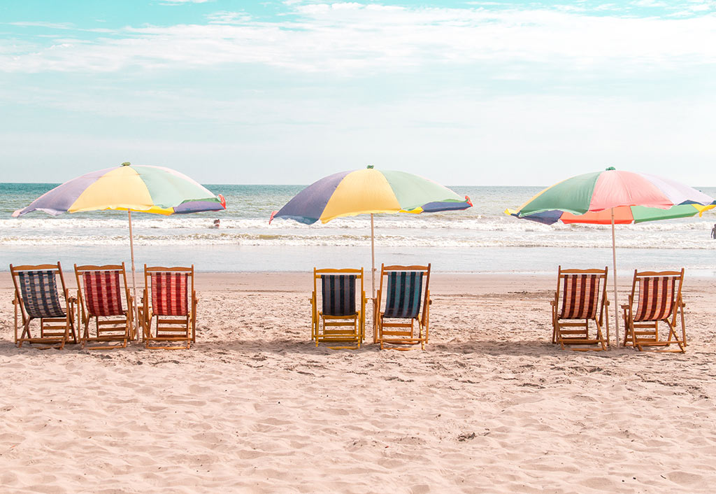 three beach umbrellas and six beach chairs on the beach in Montanita, Ecuador