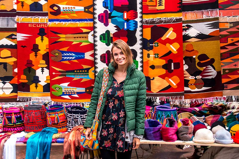 woman in green jacket standing in front of the red rugs and bags in Otavalo market