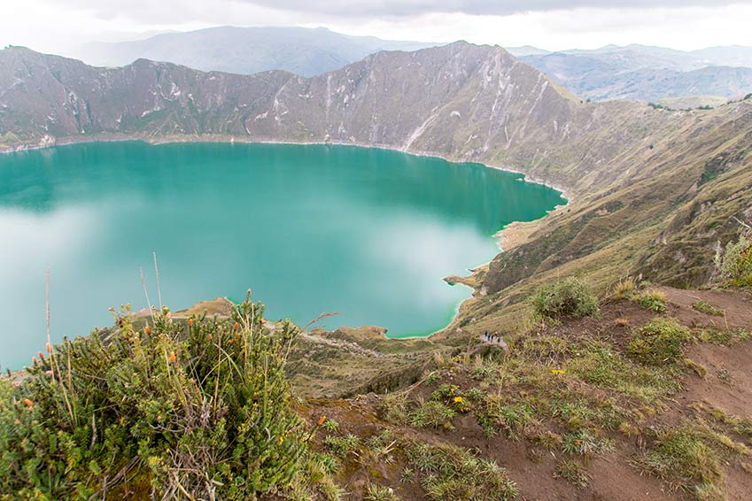 Quilotoa lake with green water, green bush and mountains