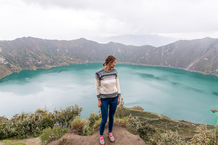 a woman standing in front of the blue lake, mountains and green grass in Quilotoa lake, Ecuador