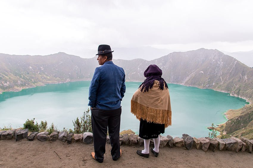 two people standing in front of blue Quilotoa lake and mountains