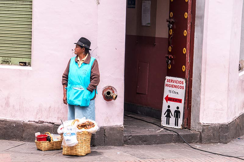 woman in blue vest sanding in front of the pink wall and selling goods in Quito, the capital of Ecuador