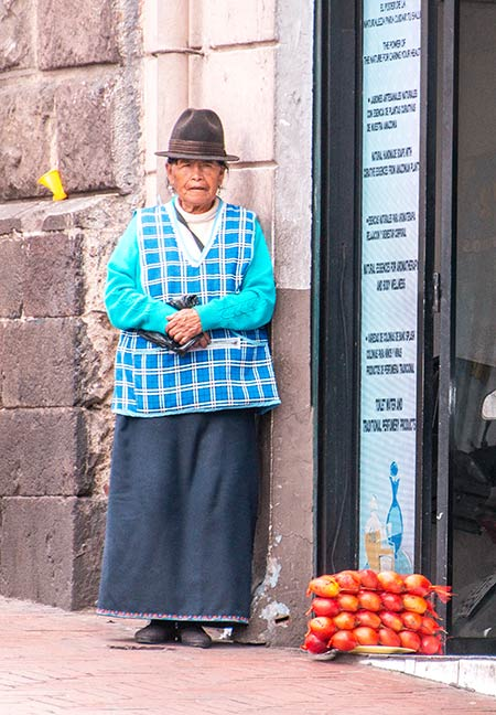 woman in blue sweater selling onion in the capital of Ecuador, Quito