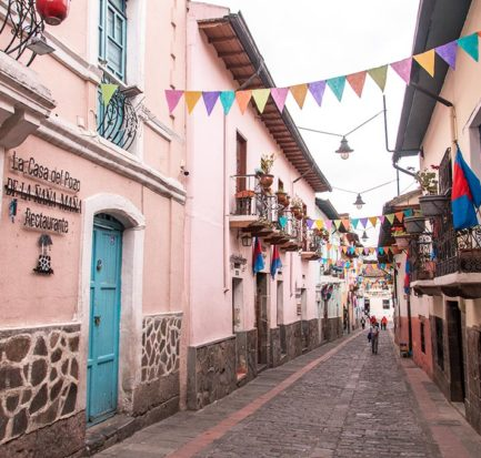 colourful La Ronda street with pink walls, turquoise door in Quito, Ecuador