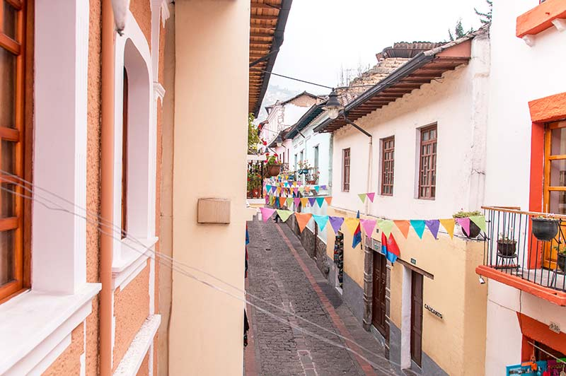 colourful street with pastel orange houses and colourful ornaments hanging on the lanes