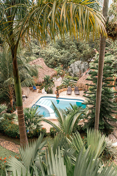 a woman sitting at the pool  with green palm trees and wooden huts at Hostal Monte Verde