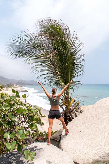 a woman standing on the rock looking out at the ocean with green palm tree and plants