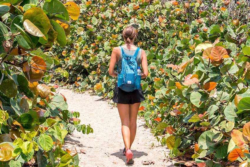 a woman walking on the white sand among orange and green leaves in Tayrona national park