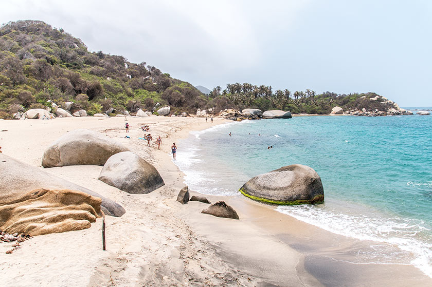 people swimming on the beach at Tayrona, rocks on the beach, white sand and blue water
