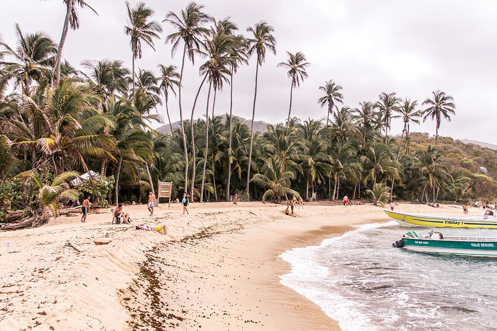 golden sand with palm trees, people and a blue boat in Cabo San Juan beach in Tayrona National park