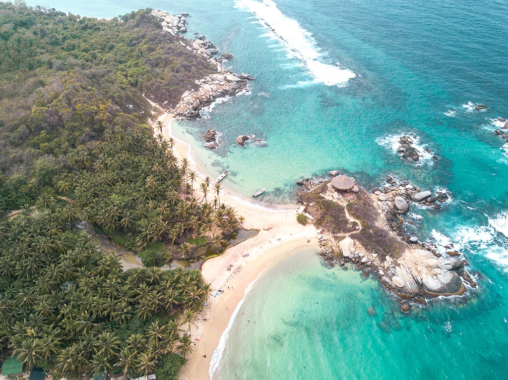 an arial shot on Cabo San Juan beach in Tayrona, wooden hut, blue water, white sand and palm trees