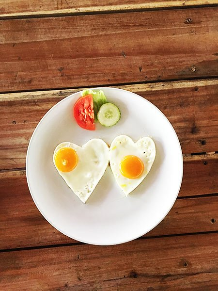 two eggs in a shape of heart with cucumber and tomato on a white place and brown table