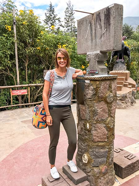 a woman standing next to the pillar with an egg in Mitad del Mundo