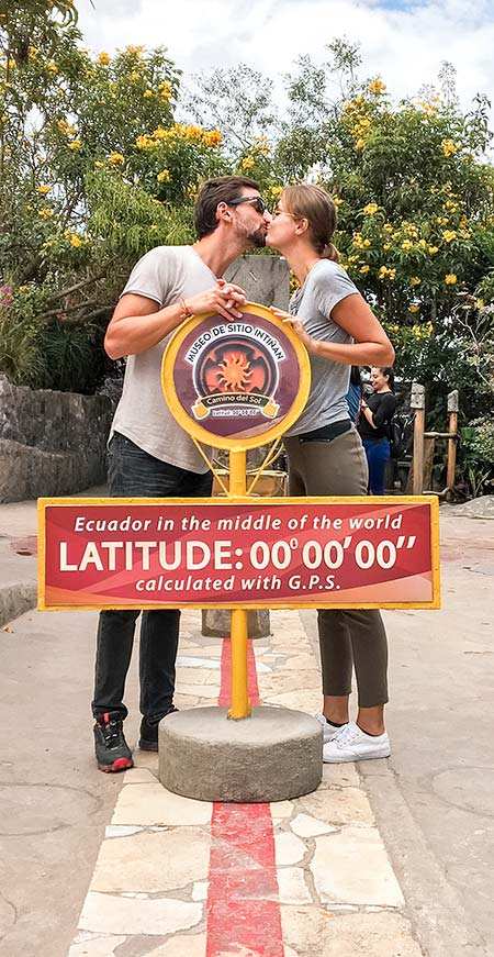two people kissing in front of the Latitude sign and red lane in Mitad Del Mundo