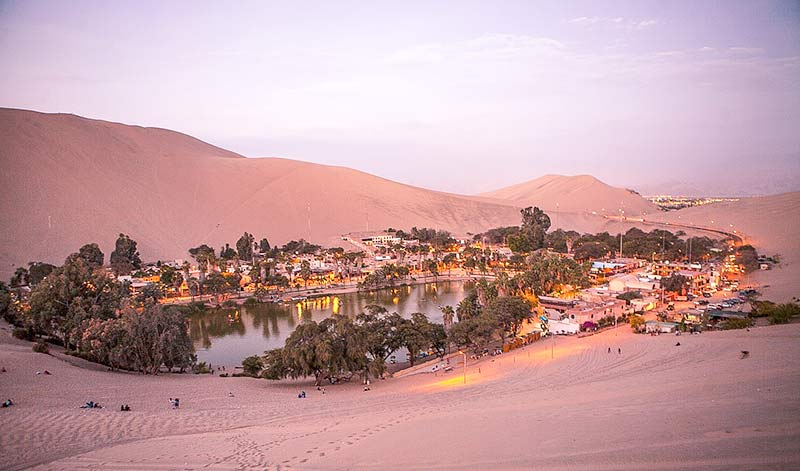 pink sky and sand dunes overlooking Laguna de Huacachina