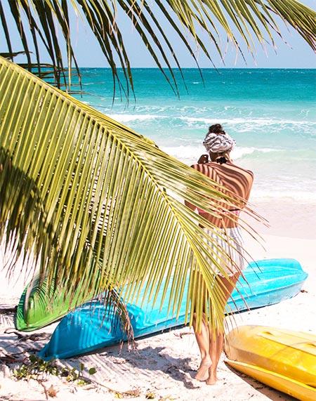 woman walking towards blue ocean, palm trees, blue, green and yellow kayaks