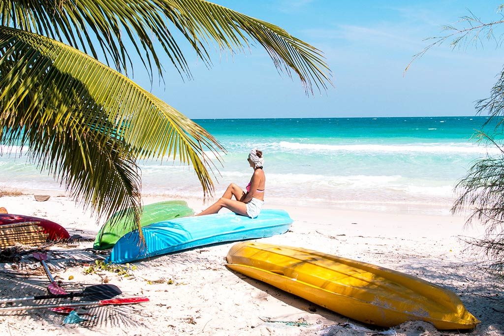 girl sitting on the blue kayak looking at the blue ocean, palm trees and yellow and green kayak on Koh Rong in Cambodia