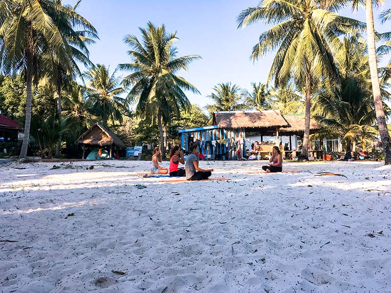 four women doing yoga on white sand beach, with palm trees and houses in the back-round