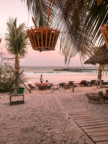 pink skies, palm trees and chairs on the beach