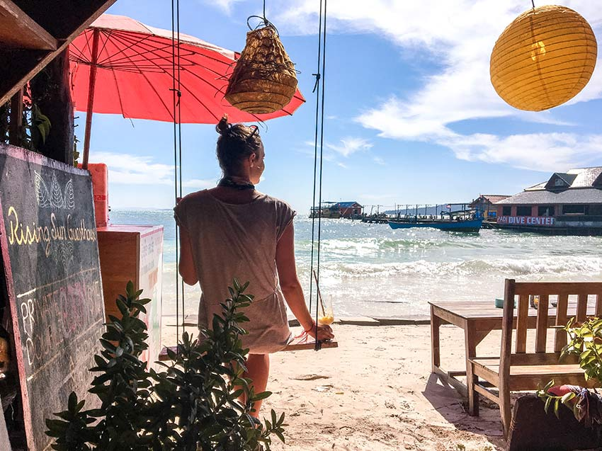 woman in grey dress siting on the swing in the restaurant on Koh Rong looking out at the ocean, red umbrella and yellow lam-pinions