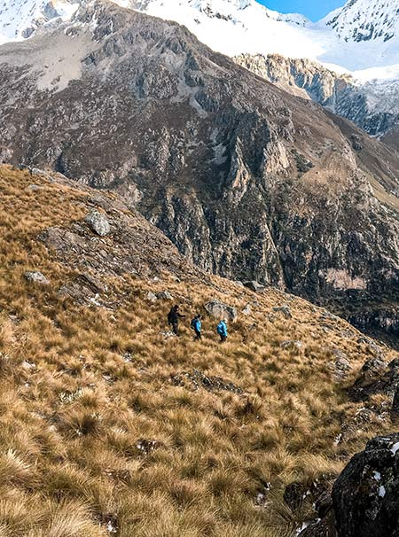 three people walking among the mountains in Peruvian Andes