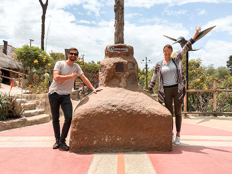 two people standing next to the stony pillar and the  white equatorial line passing through