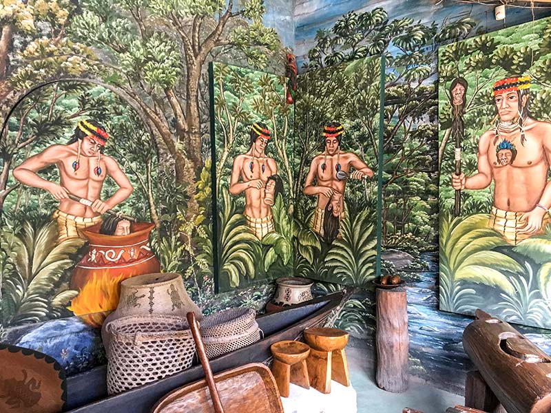 a green wall with half naked people, pottery around