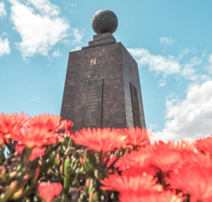 red flowers and grey monument at Mitad Del Mundo, Ecuador