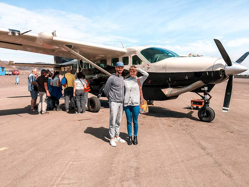 two people taking a photo in front of a plane and more people are getting to plane