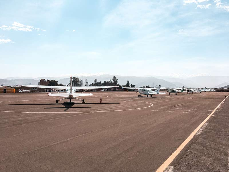 a view on the runway with a few airplanes in Nazca airport