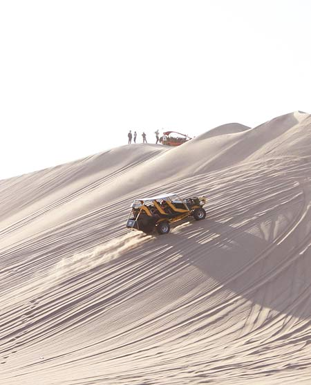 a buggy car driving through the sand hill