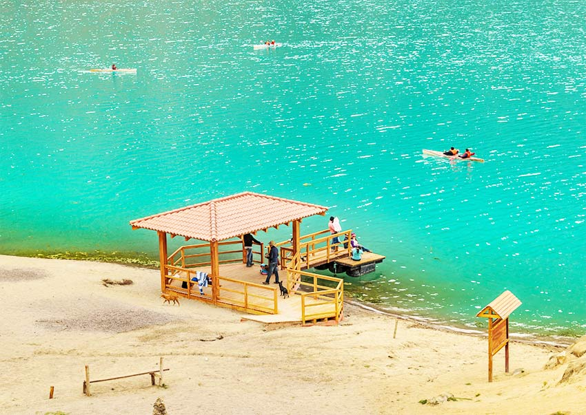 a wooden hut with people and one kayak, surrounded by turquoise waters