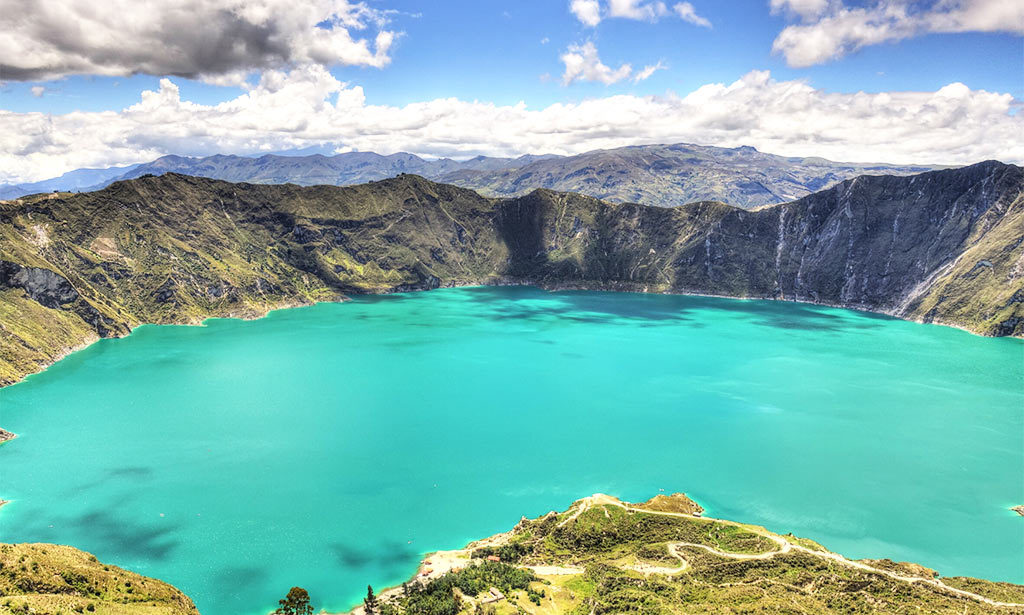 lake with turquoise water, mountains in the background and green grass in Quilotoa lake, Ecuador