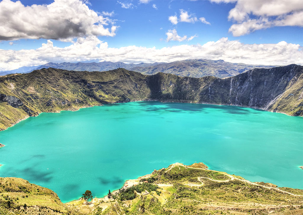 lake with turquoise water, mountains in the background and green grass in Quilotoa lake, Ecuador, one of the prettiest dreamy bucket list destinations