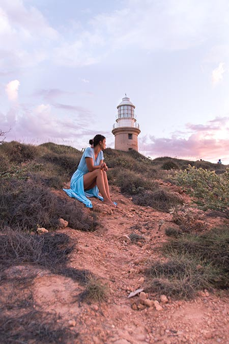 woman in a blue dress sitting in front of the lighthouse in Exmouth, Australia