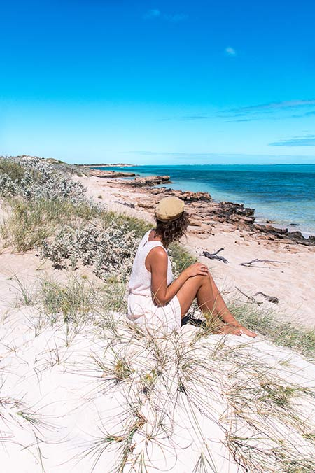 woman with a brown cap sitting on the white sand beach, blue water, and green grass in Exmouth, Western Australia