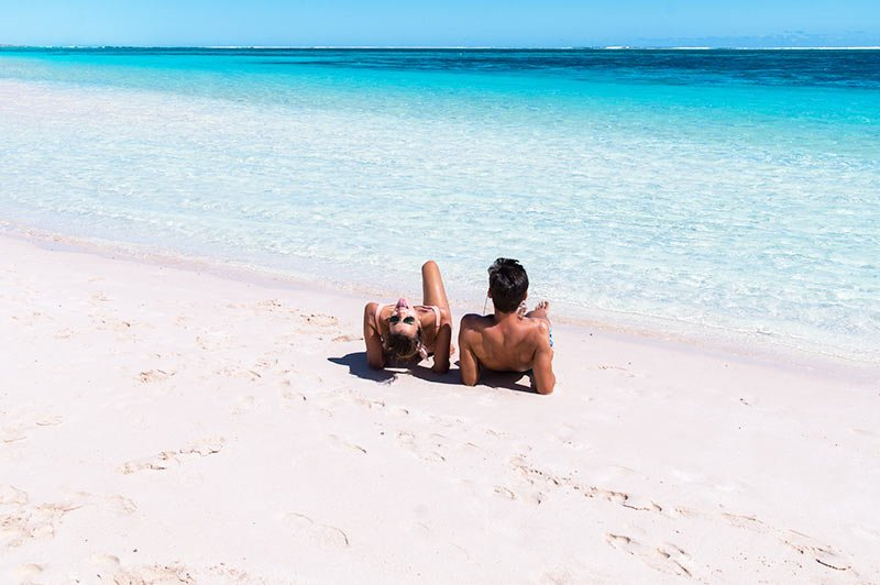 two people sitting on a white sand beach with turquoise water in Turquoise bay in WA