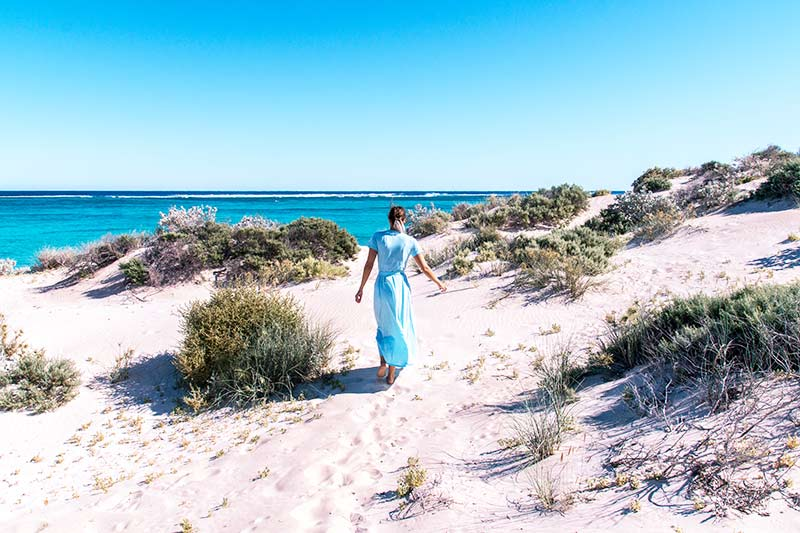 women in a blue dress walking on the white sand beach, blue water and green bush.