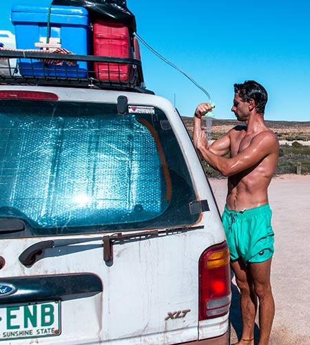 a men taking a shower near the white car
