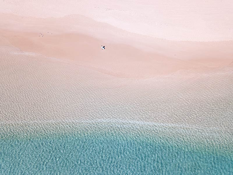 Aerial shot on blue water, woman in a blue dress and white sand near Exmouth, Australia