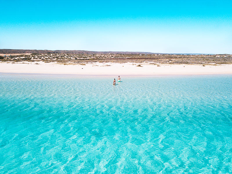 an arial shot on blue waters, white sand and two people standing in the water in Sandy Bay
