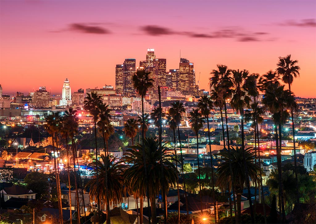 a viewing sunset which is one of the best things to do in downtown LA, pinky-orange sky, palm trees, sky scrapers.