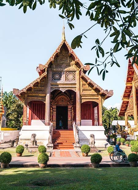 Red and Golden temple Wat Phra Singh with green grass