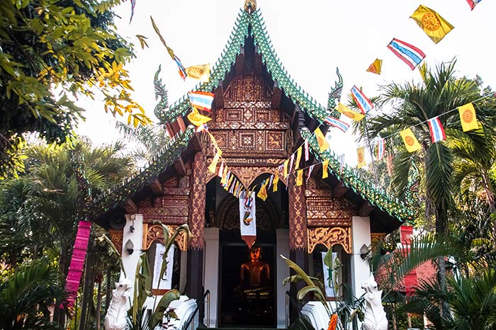 brown Thai temple with red flags and green trees around